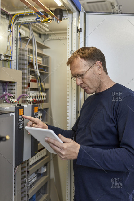 Electrician with tablet adjusting circuitry at junction box