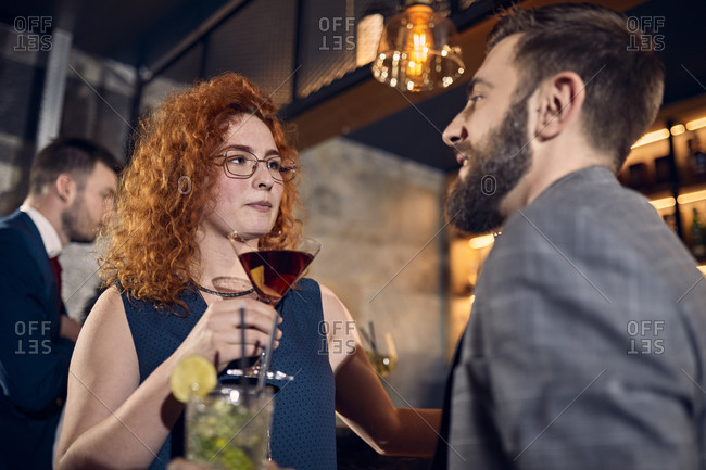 Couple with drinks talking in a bar