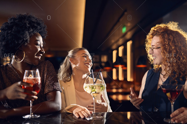 Happy friends socializing in a bar with cocktails