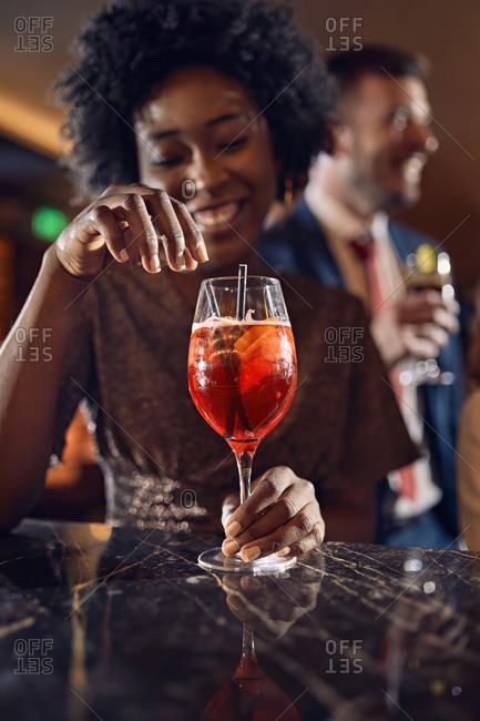 Happy woman having a cocktail in a bar