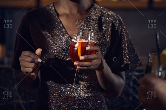 Close-up of woman holding a cocktail glass in a bar