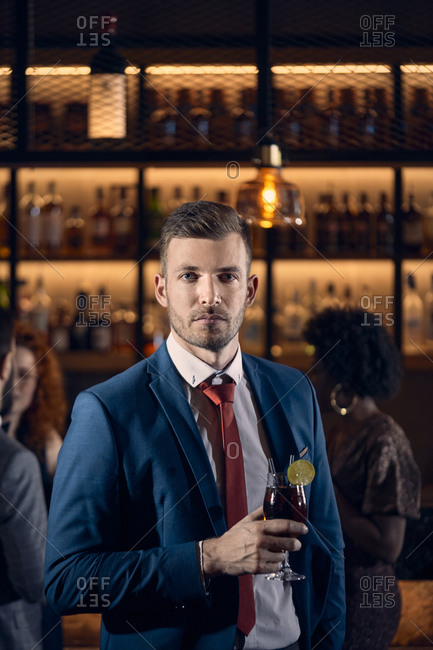 Portrait of a serious young man having a cocktail in a bar