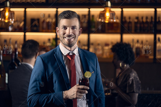 Portrait of a happy young man having a cocktail in a bar