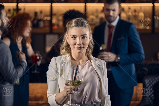 Portrait of a young woman having a cocktail in a bar