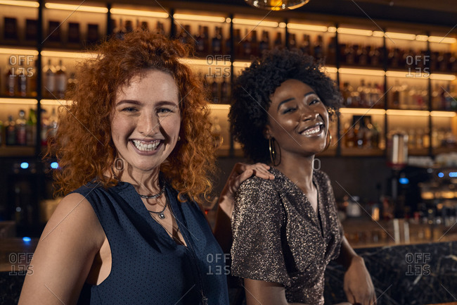 Portrait of two happy young women in a bar