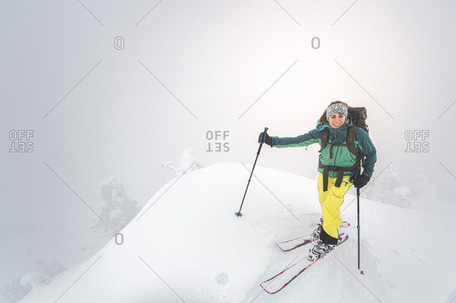 Young woman smiling backcountry skiing on snowy summit in Squamish