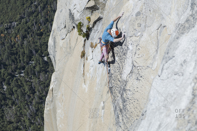 Climber looking down at his feet high up on El Capitan exposed