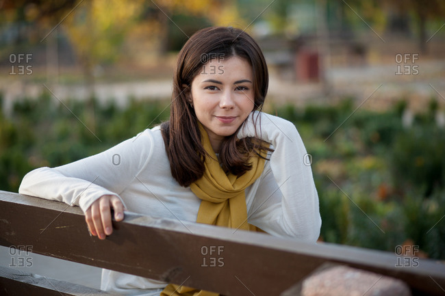 Beautiful brunette girl resting in the autumn in the park on a bench
