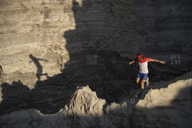 One man trail running down through a ridge on a sandy terrain