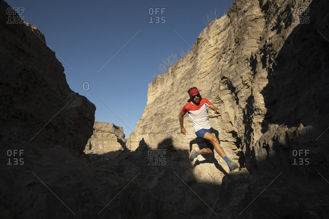 One man trail running on a small canyon with high contrast light