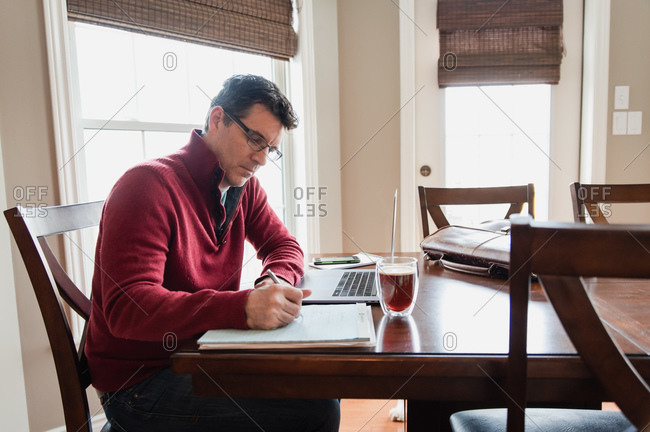 Man in glasses working from home using a computer at a dining table.