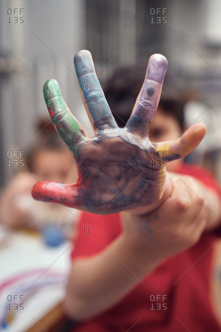 Boy shows his water-colored hand while playing with his sister