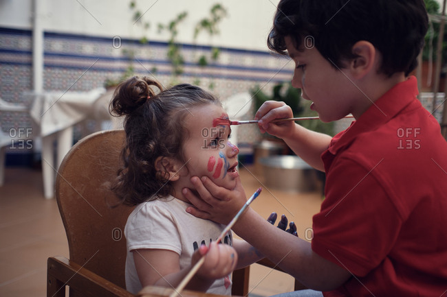 Children playing in an inner courtyard and painting with water paints