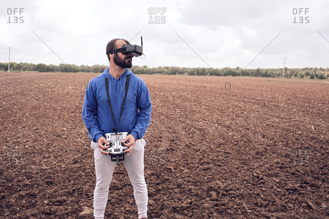 Young man flies drone with glasses in the field