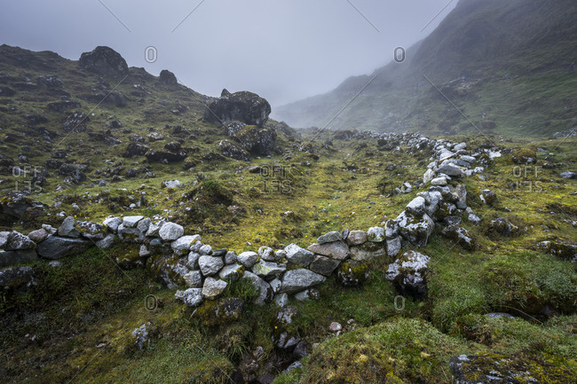 Stone wall amidst mountain during foggy weather seen from Salkan