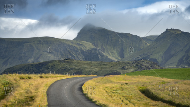 Empty road leading towards mountains in South Iceland against sk
