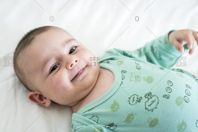 Close-up portrait of smiling toddler lying on bed at home