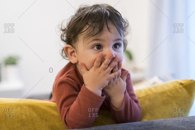 Baby boy covering mouth and looking away while standing on sofa