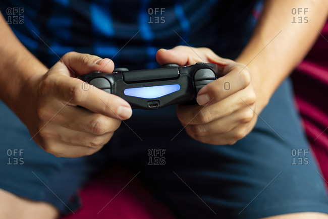 Close-up of a person playing the game console in the quarantine period