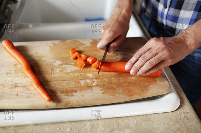 Close up of woman's hands cutting a carrot on a chopping block