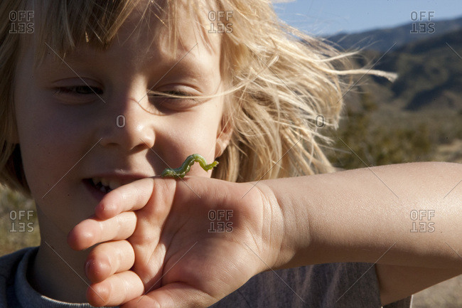 Young girl with inchworm at palm canyon trail
