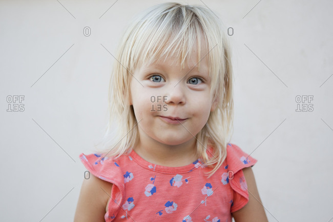 Blonde toddler girl looks mischievously at the camera