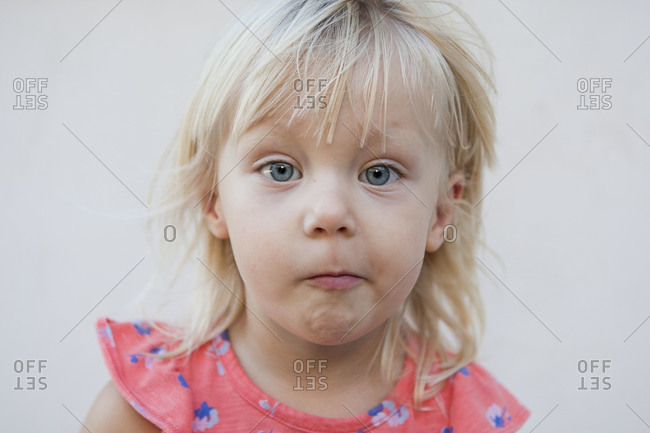 Blonde toddler girl looks frowning at the camera