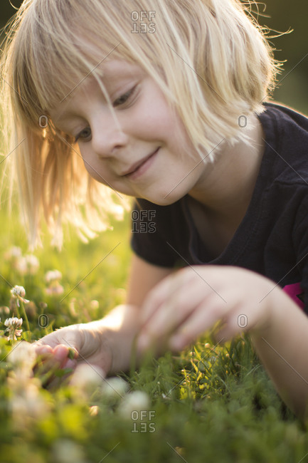 Young girl plays in the grass and wildflowers in the summer