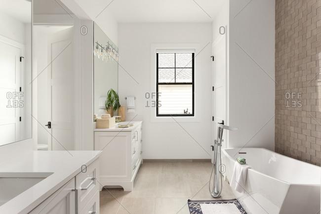 Bathroom in luxury home with two vanities and freestanding bathtub