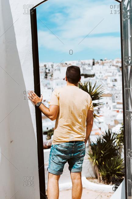 Young traveler looking through doorway over white Spanish village