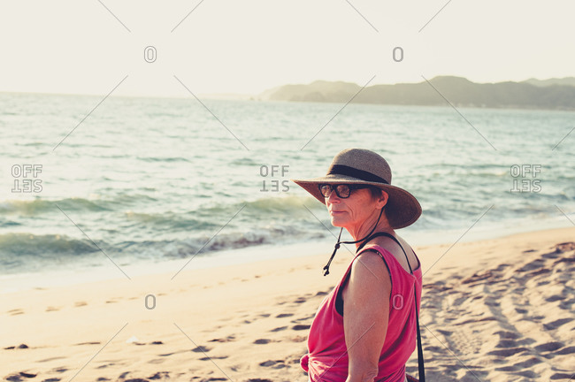 Senior woman in straw hat at the beach at sunset