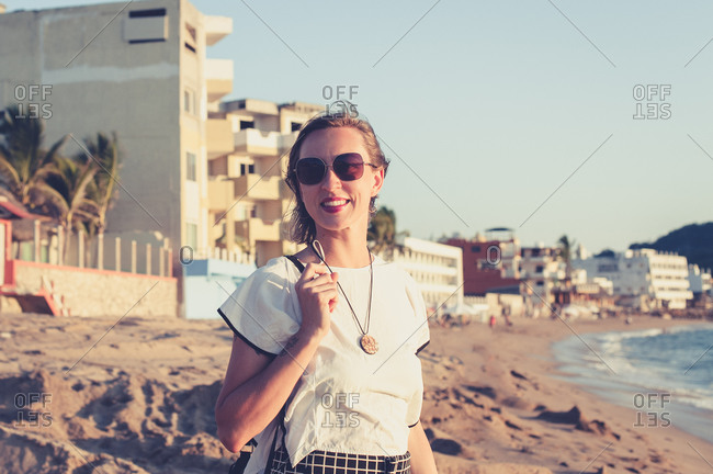 Young woman smiling at the beach at sunset
