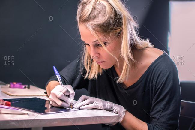 Female tattoo artist draws a tattoo