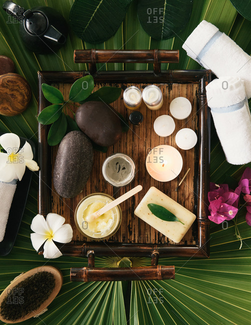 Overhead of spa kit with candles and scrubs and rubs on palm frond