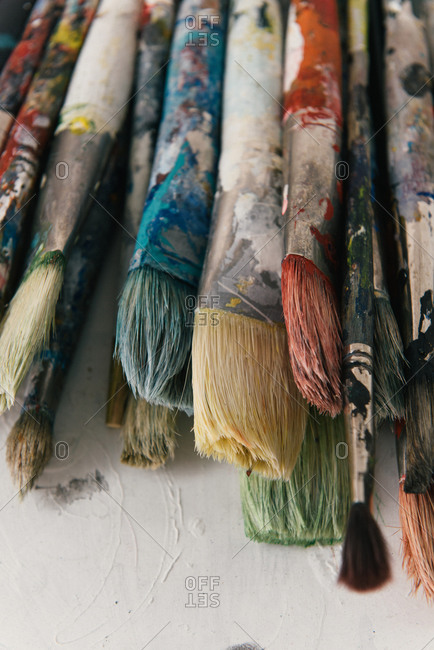 Close up of paint covered paint brushes on palette in artist studio