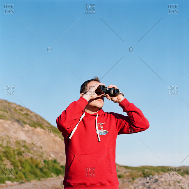 Man and woman stand at the foot of the mountain with binoculars