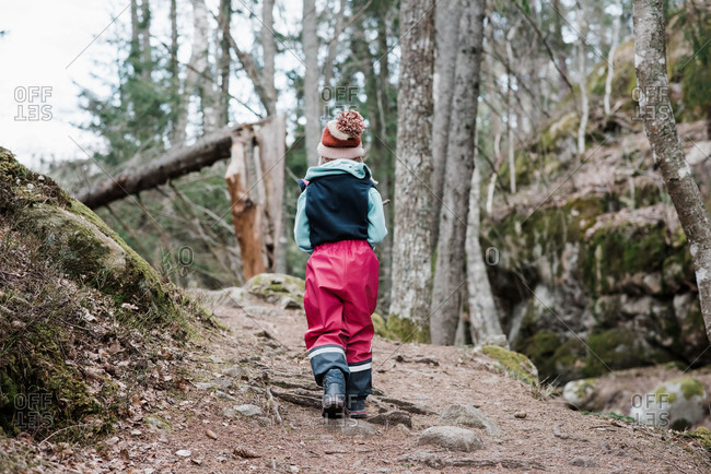 Rear view of a young girl hiking through a forest in Sweden