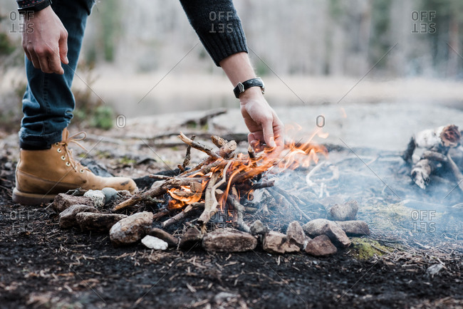 Man putting logs on a handmade campfire outdoors in Sweden
