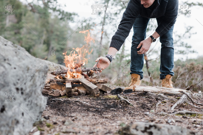 Man putting sticks on a campfire outdoors in Sweden