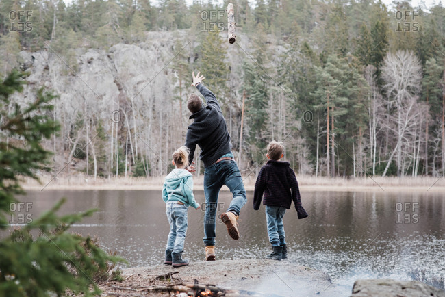 Father throwing logs into the sea with his kids whilst hiking