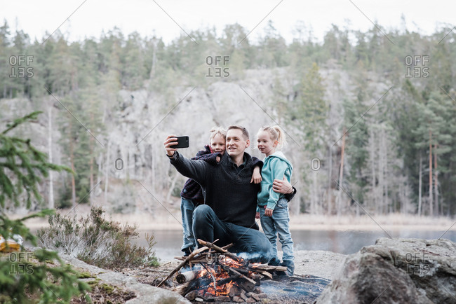 Father taking pictures with his kids whilst enjoying a campfire