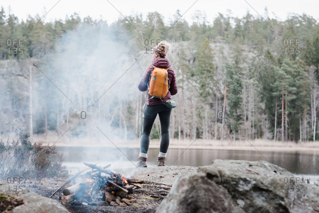 Woman standing on a rock by a campfire whilst hiking in Sweden