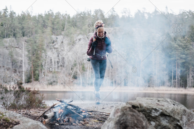 Woman walking on a rock towards a campfire by a lake in Sweden