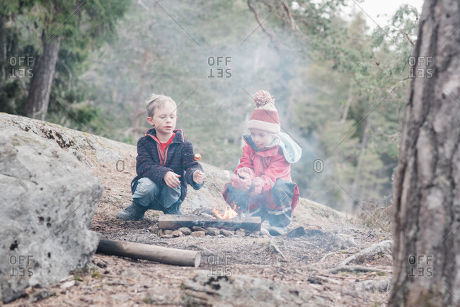 Brother and sister sat cooking marshmallows on a campfire in Sweden