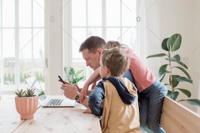 Father working from home with his kids climbing over him