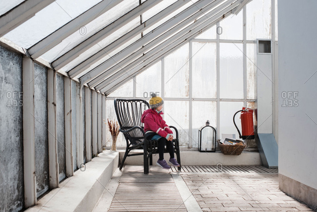 Girl sitting on a chair in a green house in winter