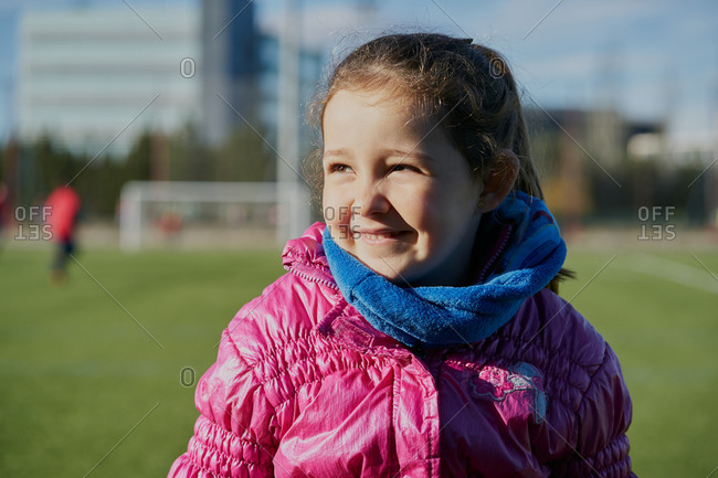 Smiling little girl wearing a pink coat in a football stadium