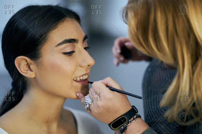 Close-up of a make-up artist touching up a model's face