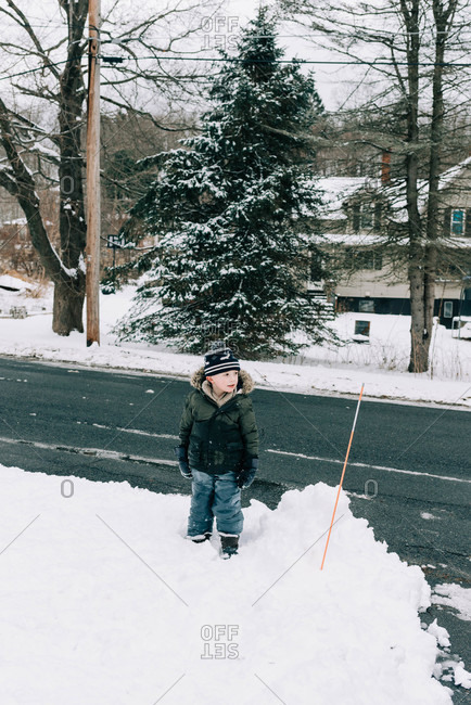 Little boy standing in the snow with his hat crooked.