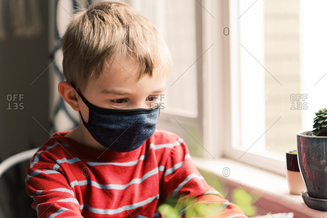 Boy missing his friends while in self isolation over the coronavirus.